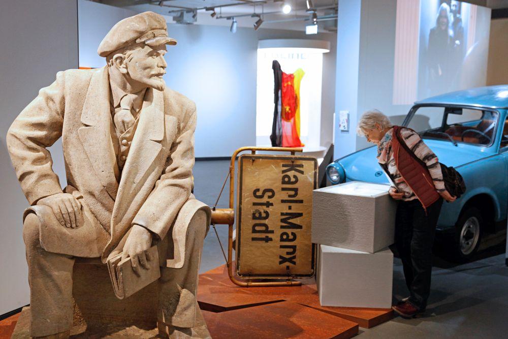 Besucherin neben der Skulptur von Skulptur von Lenin