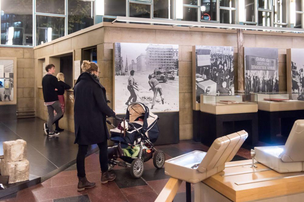 Eine junge Frau geht mit einem Kinderwagen in die Ausstellung, es sind großformatige Fotos und geöffnete Koffer zu sehen