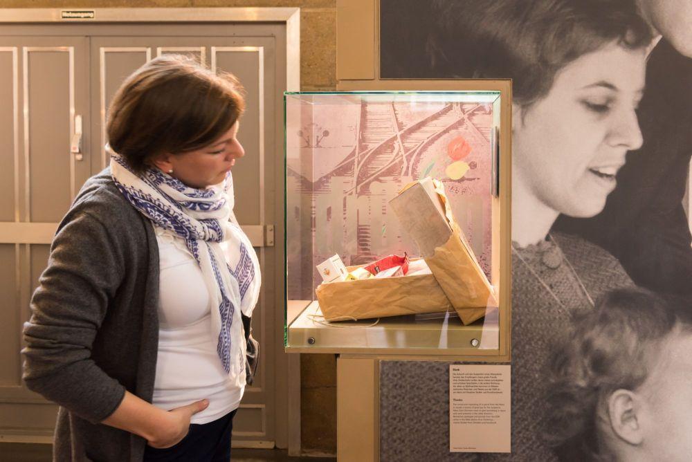 Eine Frau steht seitlich vpr einer Vitrine mit einem geöffnete Paket, darin verschiedene Westdeutsche Produkte, im Hintergrund ein großformatiges Fotos mit einer jungen Frau