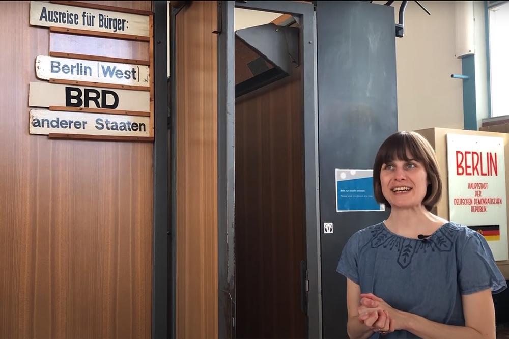 Besucherbegleiterin Jenny Baumann vor einer originalen Passkontrollkabine im Tränenpalast