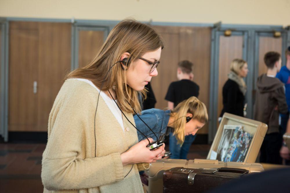 Besucherin mit Kopfhörern betrachtet einen Monitor im Tränenpalast