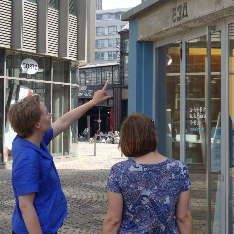 Zwei Frauen stehen vor dem Tränenpalast, im Hintergrund ist der Bahnhof Friedrichstraße zu sehen.
