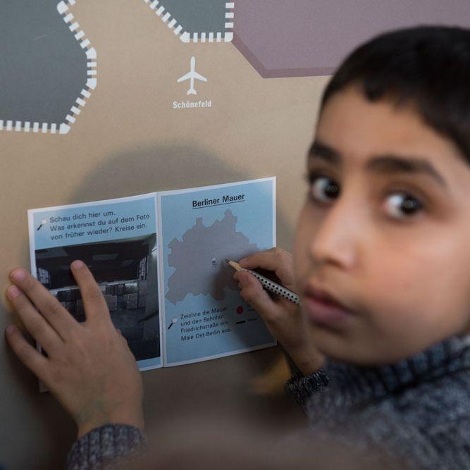 Ein kleiner Junge hält ein kleines, aufgeschlagenes Heft gegen eine Wand, um etwas einzuzeichnen