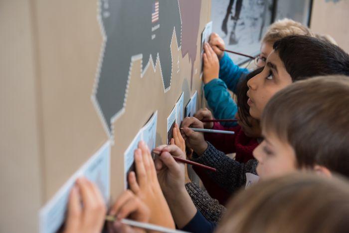 Kinder füllen ein Heft während eines Workshops aus