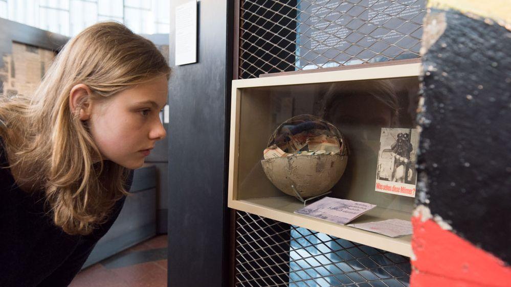 Eine Praktikantin im Tränenpalast schaut sich ein Objekt an