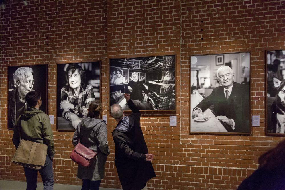 Besucher vor einer Wand mit Fotos