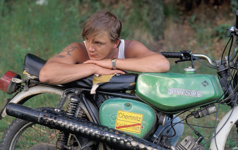 Ein junger Mann lehnt sich nachdenklich über sein Motorrad.