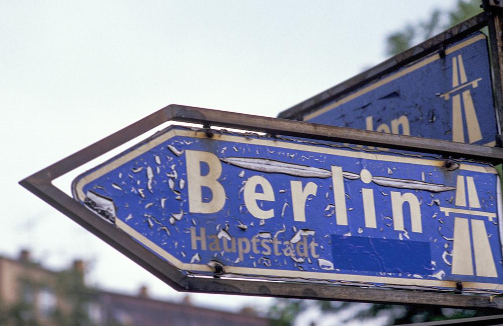 Blaues Verkehrsschild, das den Weg zur Hauptstadt Berlin angibt und nach links zeigt.