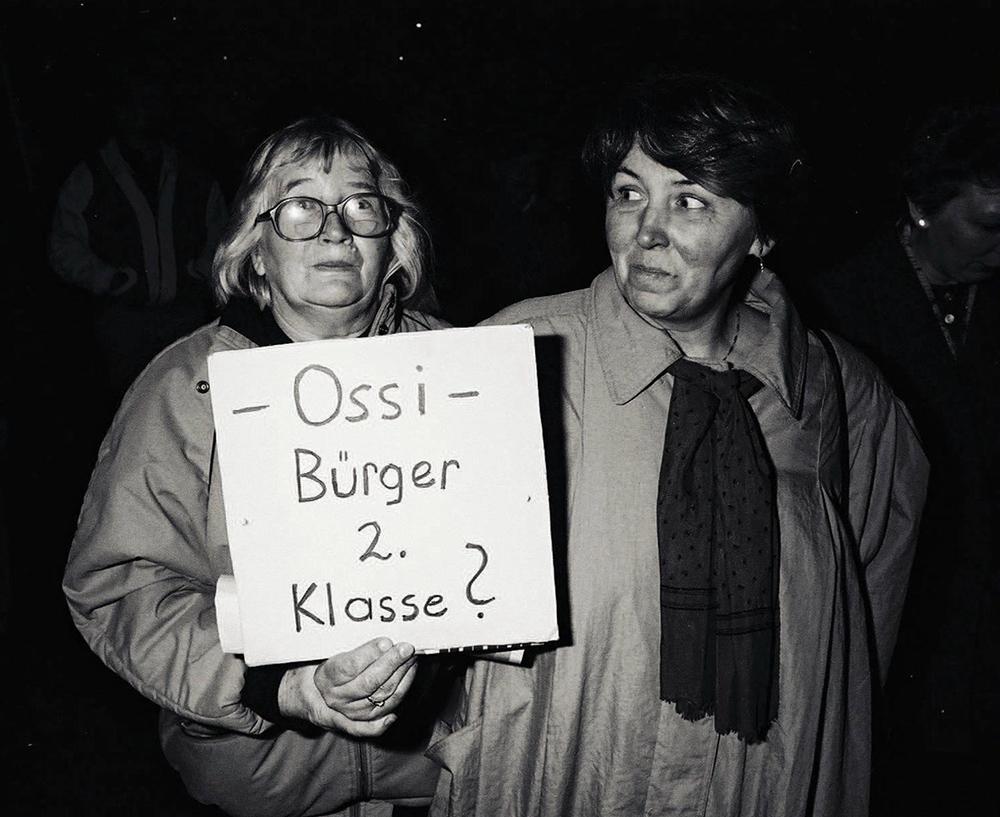 Fotografie in schwarz-weiß. Darauf sind zwei Frauen zu sehen. Die linke hält ein Plakat hoch, auf dem steht: Ossi. Bürger zweiter Klasse? Die rechte Frau schaut die linke Frau an.