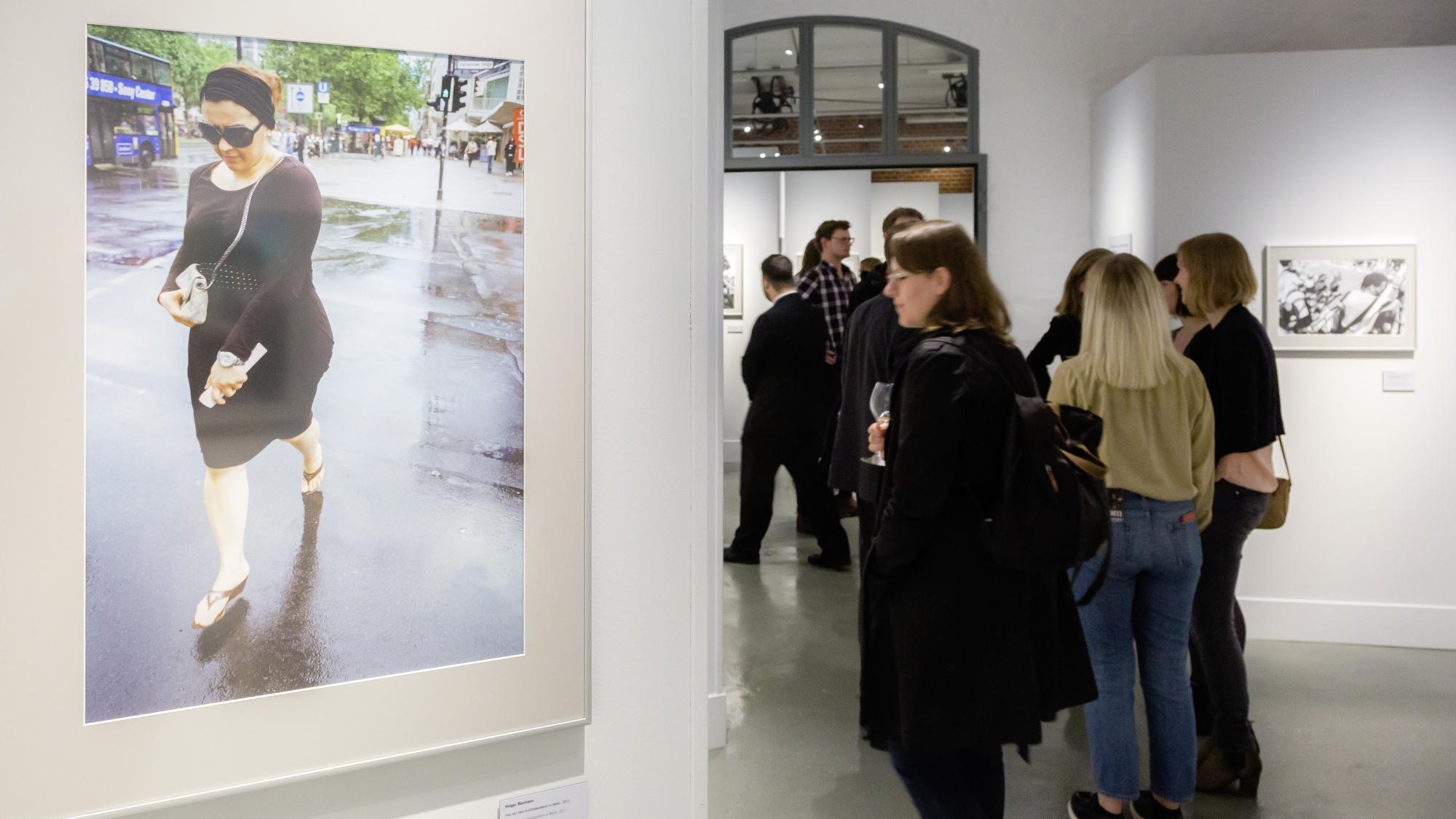 Besucher in einem Ausstellungsraum mit weißen Wänden, im Vordergrund eine Frau mit Kleid, Sonnenbrille und Handtasche.
