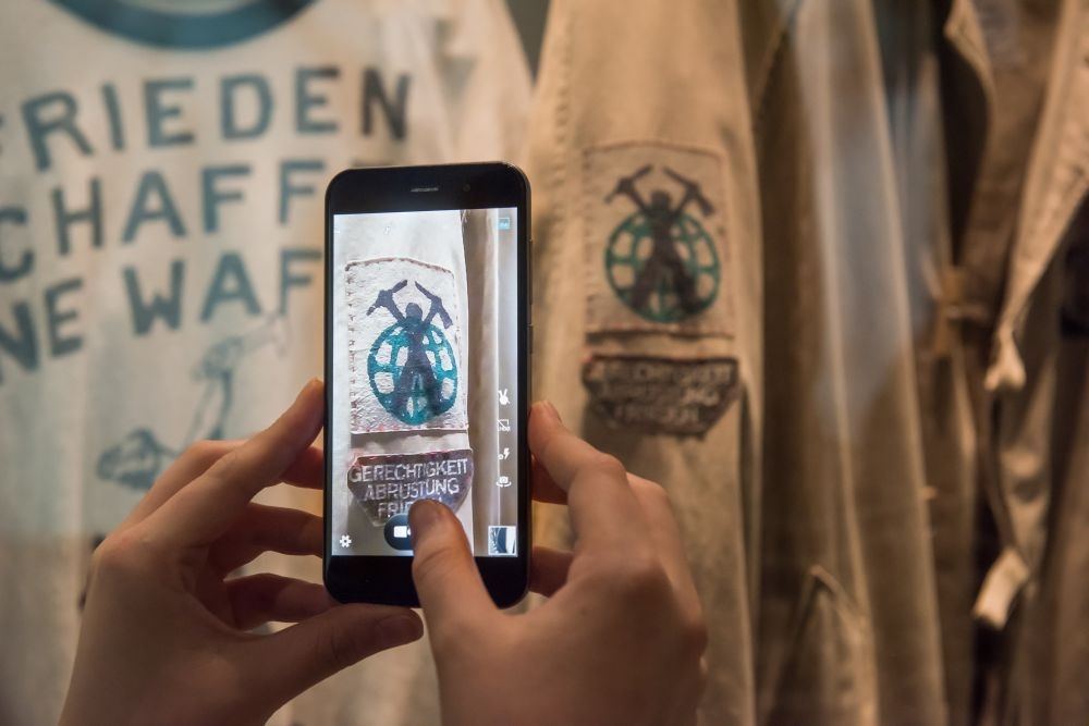 Two hands are holding a smartphone to take a picture of the self-made clothes of the peace movement
