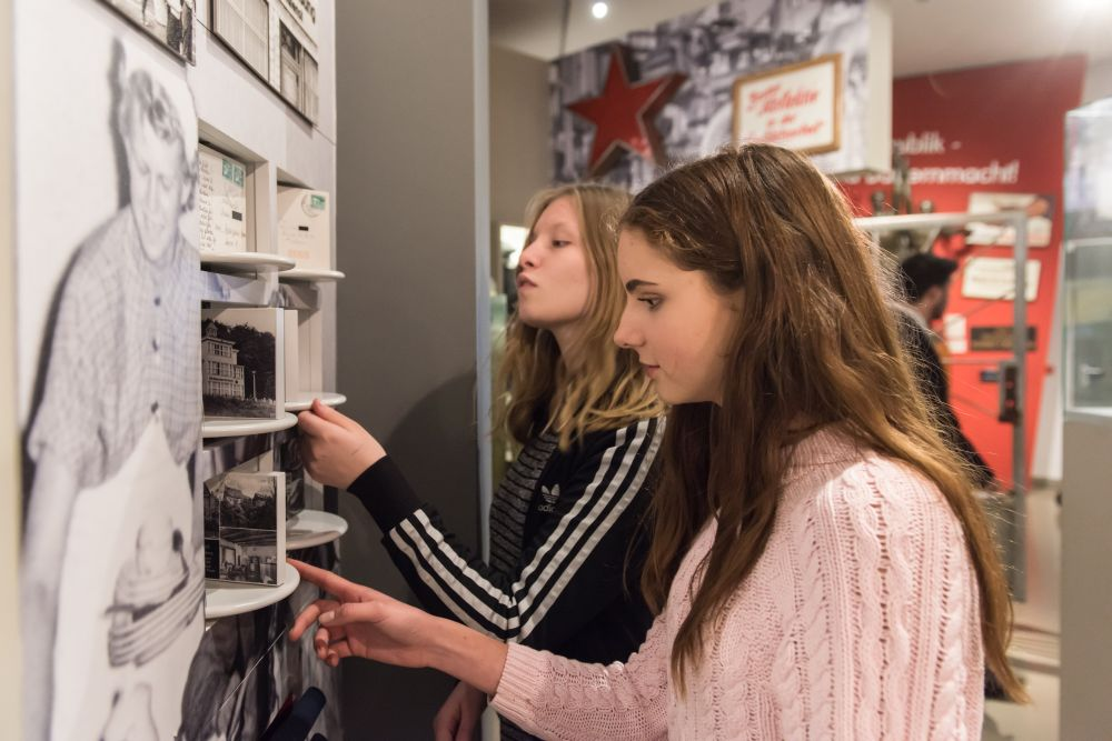 Two young girls are looking at photographs in the exhibition 'Everyday Life in the GDR'
