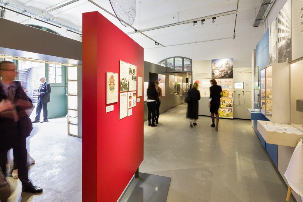 Besucher in einen großen Ausstellungsraum mit Fotos und Vitrinen und einen großen Türrahmen zu einem dahinterliegenden Raum.