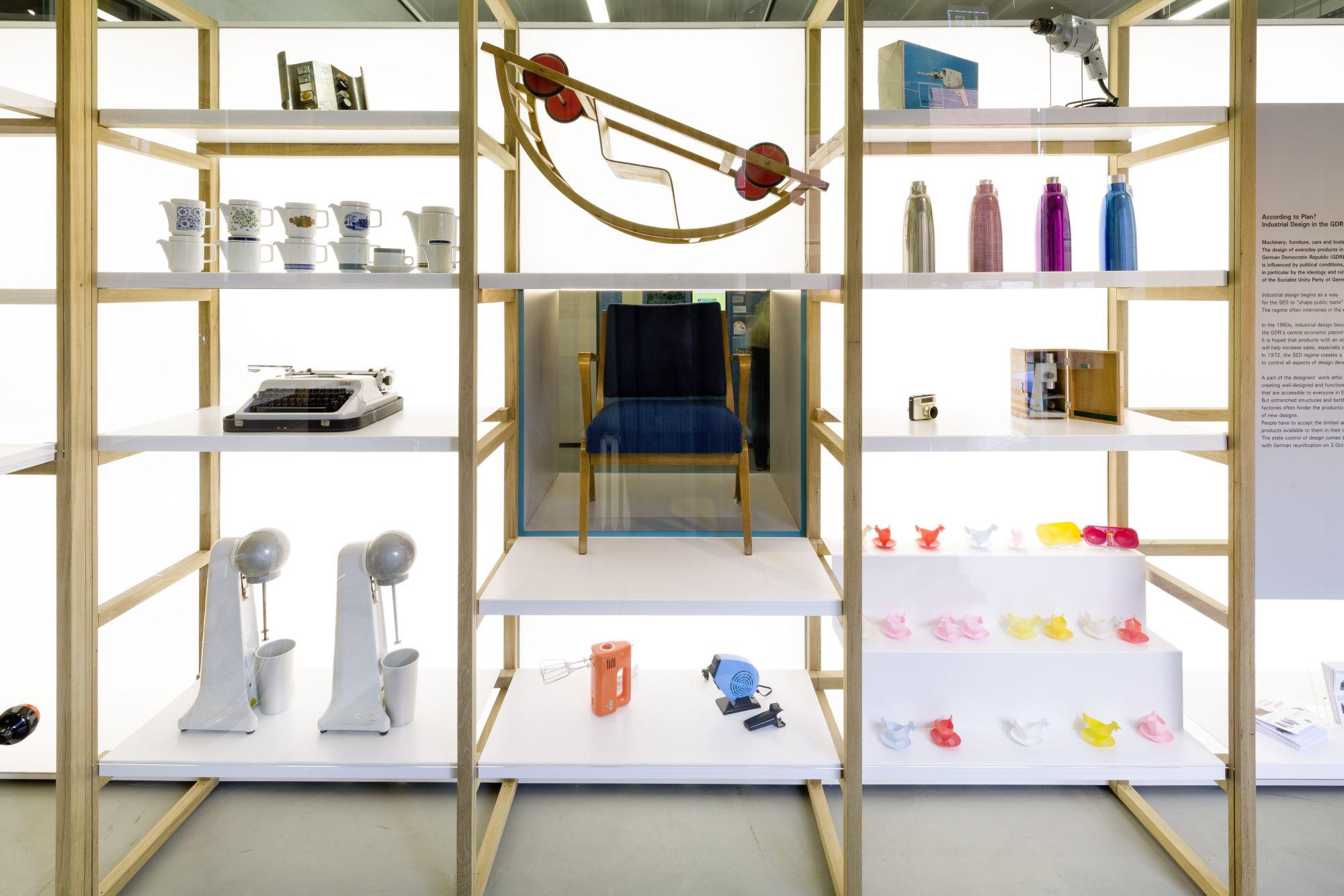 Ein großes Regal mit vielen farbigen Produkten wie Isolierkannen, Eierbechern, einem Föhn, Mixern, einer Schreibmaschine, Kaffeekännchen und einem großen Stuhl