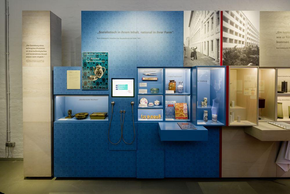 Eine große Ausstellungswand mit mehreren Vitrinen, darin Alltags- und dekorative Gegenstände wie Vasen und eine Geflügelschere.