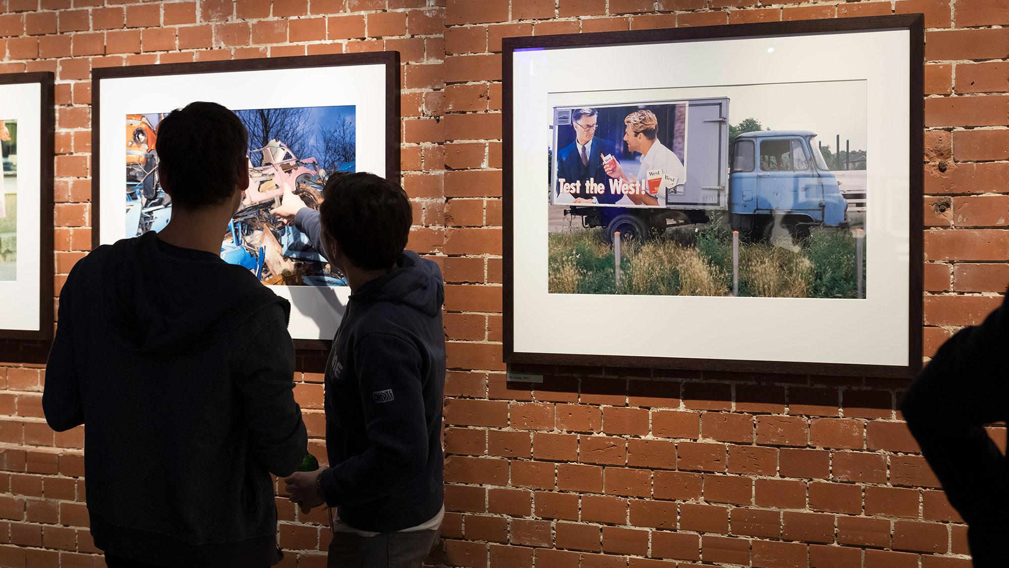"""Besucher betrachten Fotografien von Daniel Biskup in der Ausstellung """"Nach dem Mauerfall"""""""