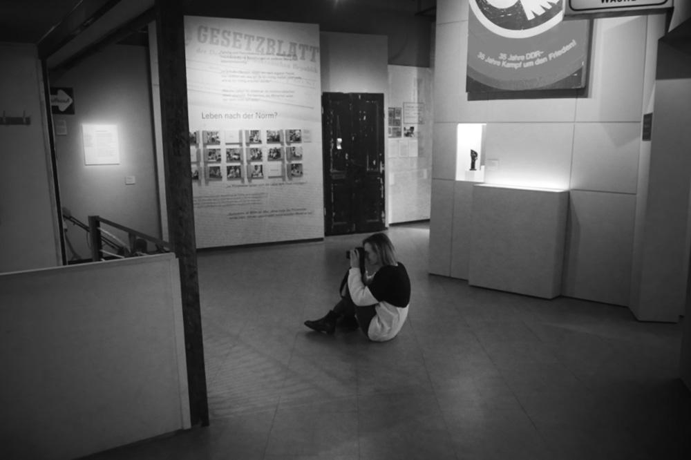 Eine Frau sitzt mit einer Kamera in der Hand auf dem Boden und fotografiert.