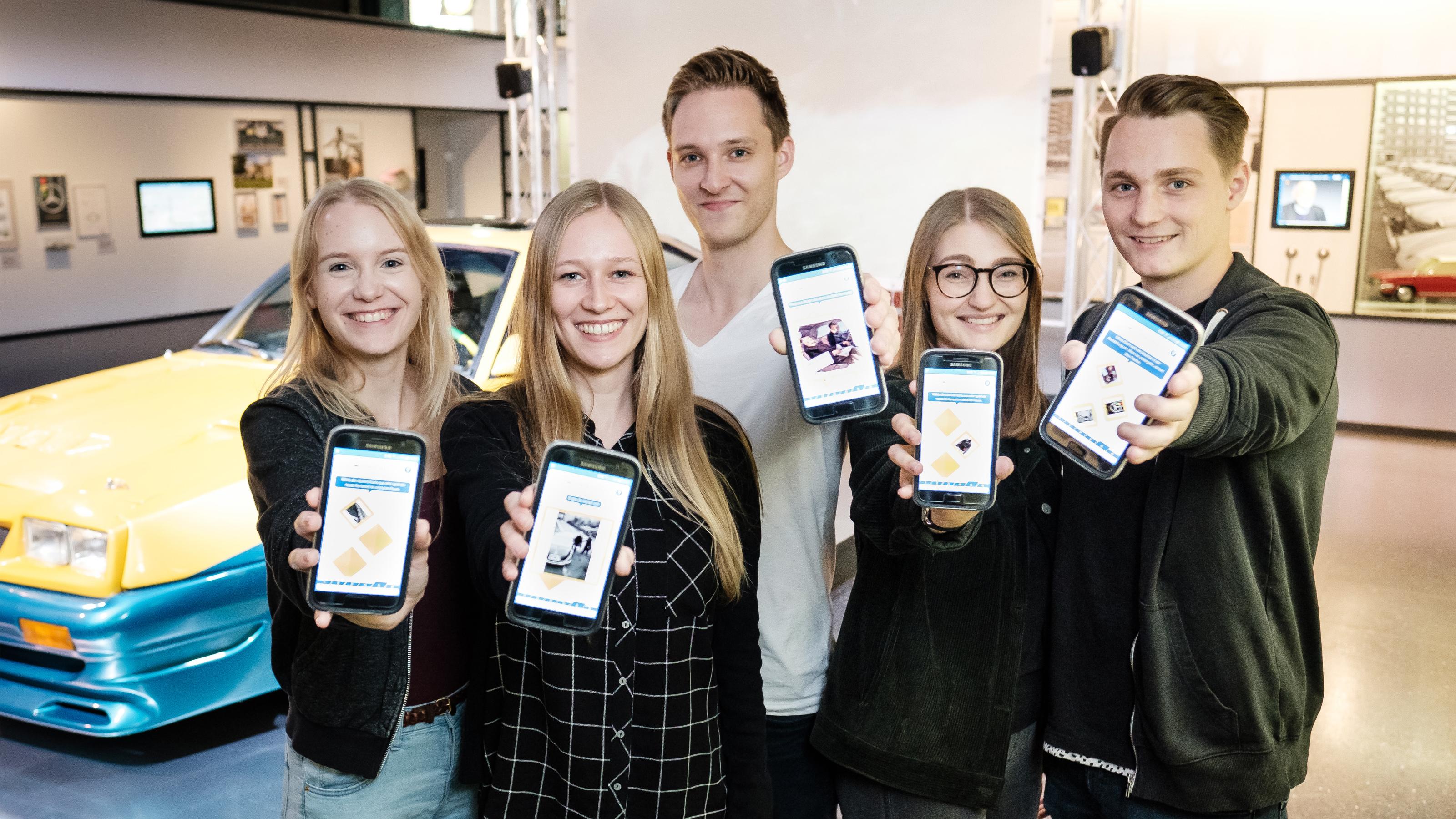 Eine Gruppe junger Menschen spielt die App in der Autoausstellung
