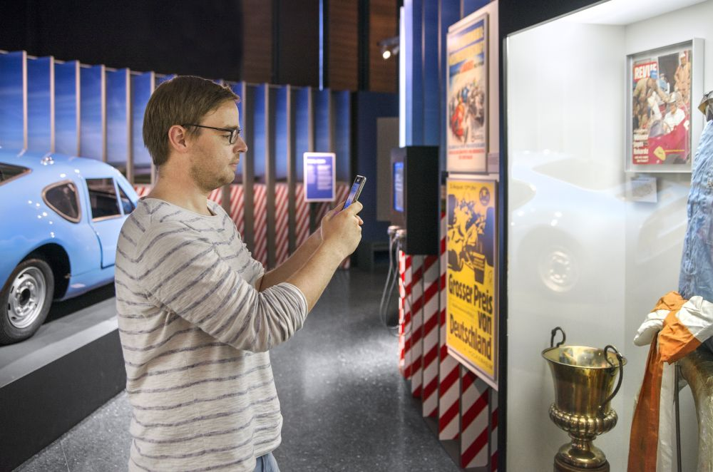 Mann spielt die App in der Ausstellung