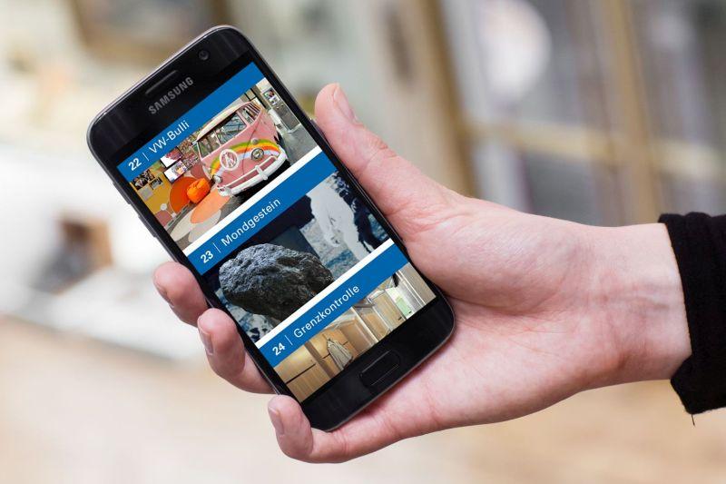 Eine Hand hält ein Smartphone mit einem Audioguide auf dem Display.