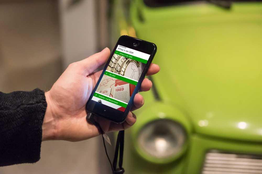 Hand mit Smartphone, auf dem Display zu sehen ist der AudioGuide zur Dauerausstellung 'Alltag in der DDR' im Museum in der Kulturbrauerei Berlin