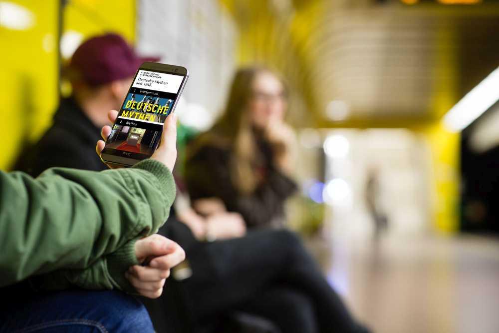 Hand mit Smartphone, auf dem Display zu sehen ist der AudioGuide mit Audiodeskription zur Wechselausstellung 'Deutsche Mythen seit 1945' im Haus der Geschichte Bonn