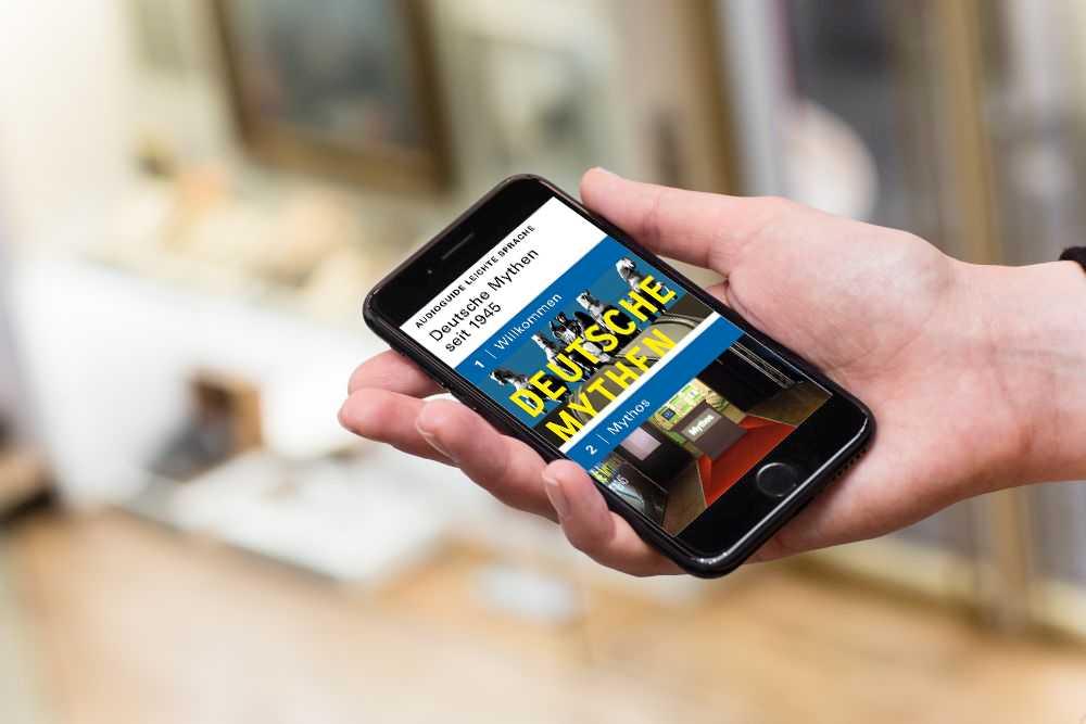 Hand mit Smartphone, auf dem Display zu sehen ist der AudioGuide Leichte Sprache zur Wechselausstellung 'Deutsche Mythen seit 1945' im Haus der Geschichte Bonn