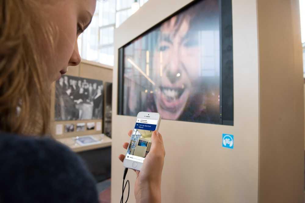 Hand mit Smartphone, auf dem Display zu sehen ist der AudioGuide zur Dauerausstellung 'Ort der deutschen Teilung' im Tränenpalast Berlin