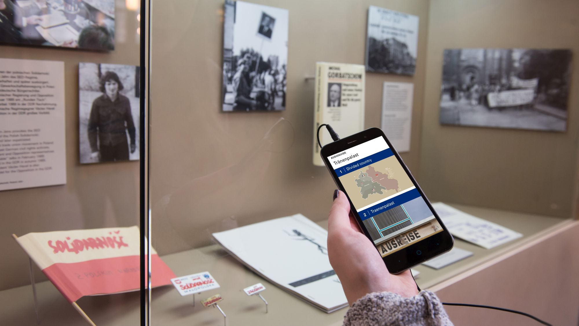 Hand with smartphone, on the display you can see the AudioGuide for the permanent exhibition 'Site of German Division' in the Tränenpalast