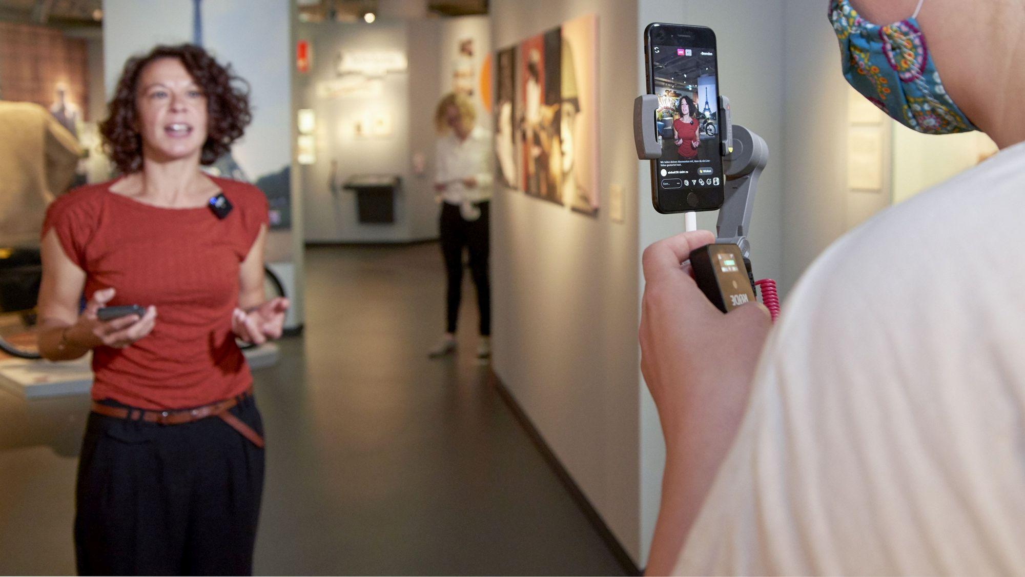 Eine Frau wird in einem Ausstellungsraum mit einem Smartphone gefilmt.