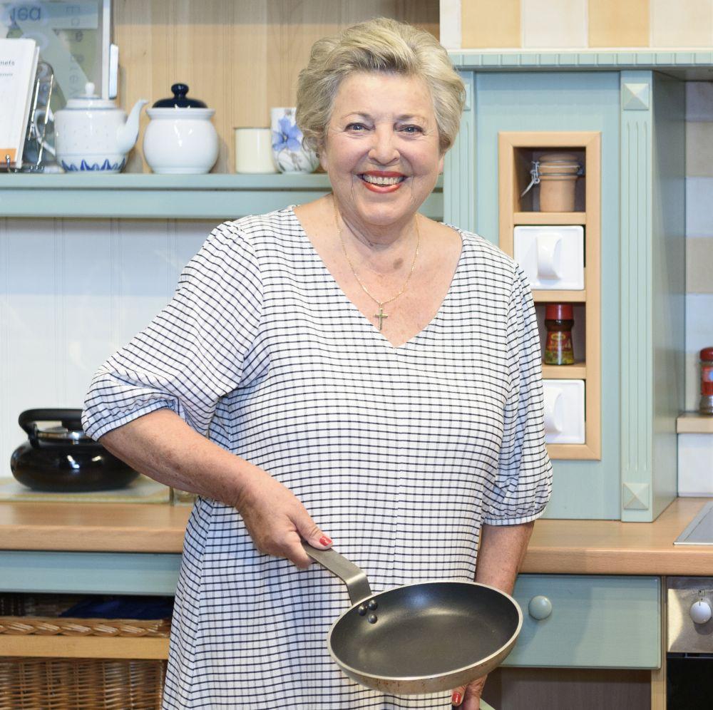 Schauspielerin Marie-Luise Marjan steht mit einer Bratpfanne in der Hand vor einer Küchenzeile.