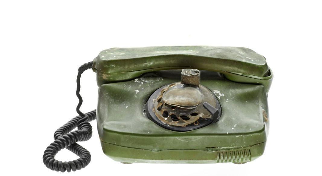 Grünes Telefon mit Wählscheibe und starken Brandspuren