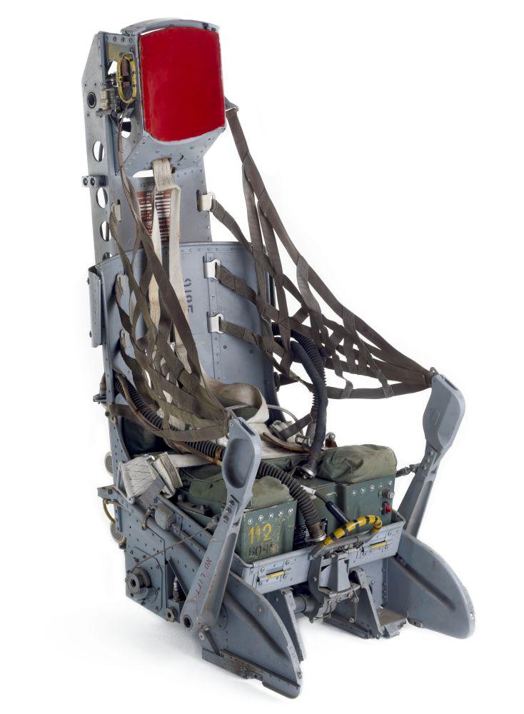 Metallener Sitz mit Kopfstütze, Armlehnen und tarnfarbenen Netzen an den Seiten