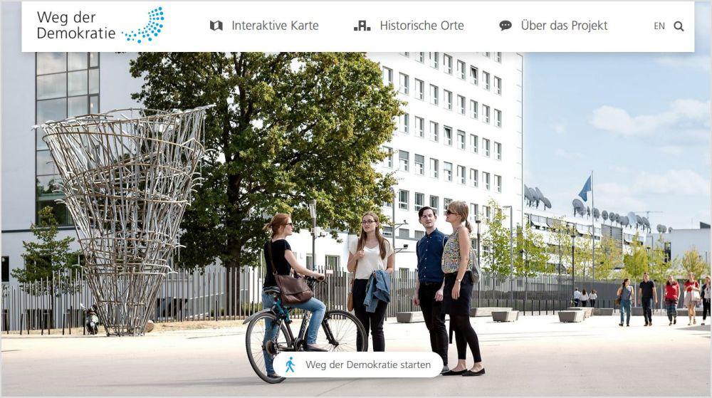 Screenshot der Webseite zum Weg der Demokratie mit einem großen Foto von Menschen auf dem Platz der Vereinten Nationen in Bonn
