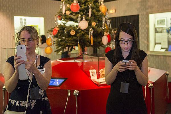 Zwei Frauen stehen vor einem ausgestellten Weihnachtsbaum und tippen in ihre Smartphones