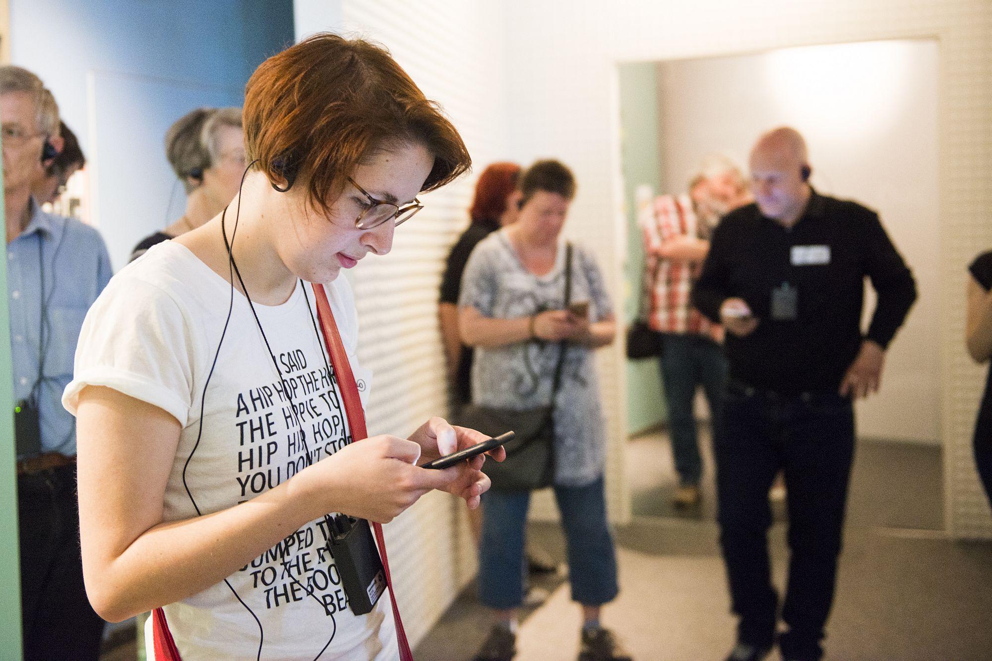 """Eine Teilnehmerin beim Tweetup zur """"Immer bunter"""" liest etwas auf ihrem Smartphone"""