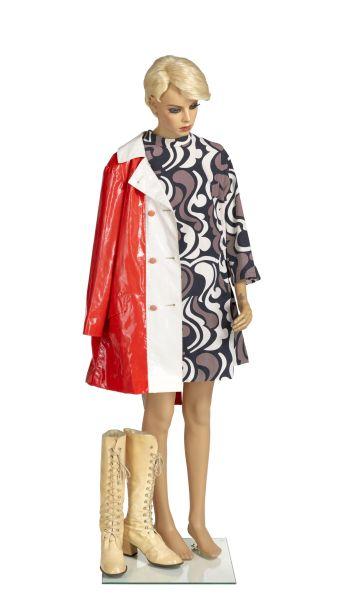Schaufensterpuppe mit einem kurzen, gemusterten Kleid, einem roten Regenmantel und beigen Lackstiefeln zum Schnüren.