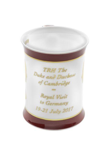 Weiße Tasse mit goldener Aufschrift unf dunkelroten Rändern.