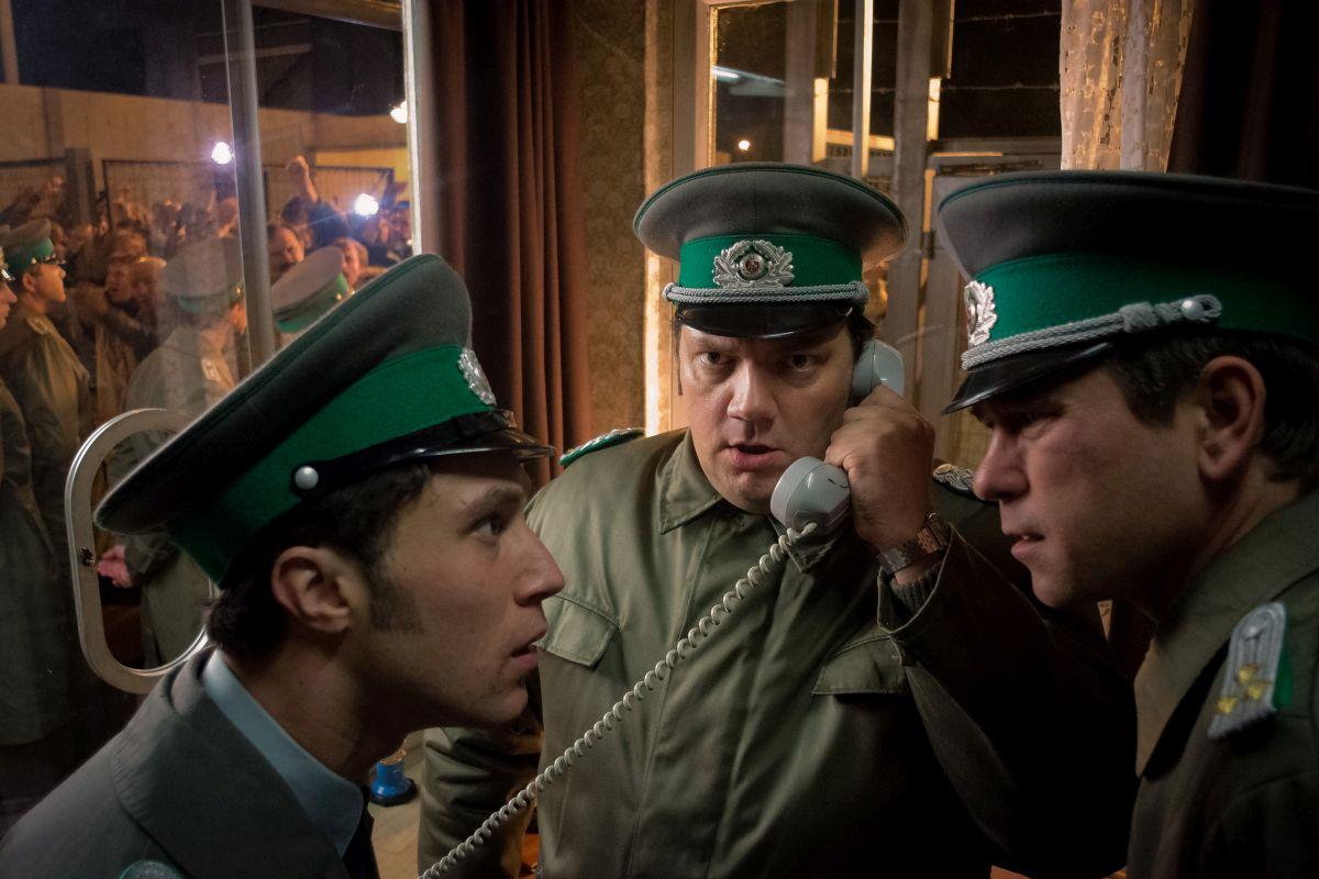 Drei uniformierte Männer stehen im Halbkreis, zwei sehen sich ungläubig direkt an, der mittlere hat einen Telefonhörer am Ohr.