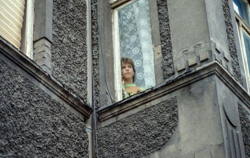 Eine junge Frau blickt aus dem Fenster eines grauen Hauses