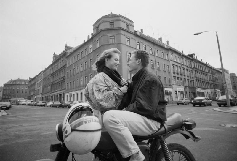 Ein Pärchen sieht sich verliebt an, der junge Mann sitzt auf einem Moped.