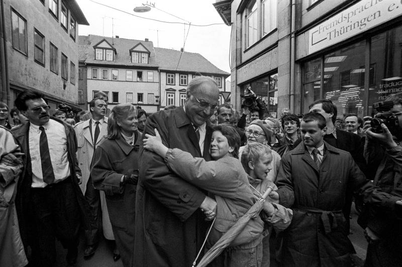 Im Zentrum des Bildes umarmt eine Person den damaligen Bundeskanzler Helmut Kohl.