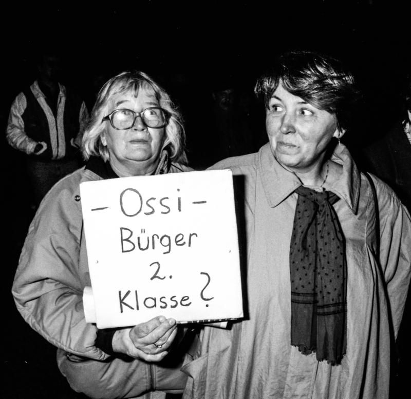 Zwei Frauen, eine trägt ein Schild mit der Aufschrift -Ossi- Bürger 2. Klasse?