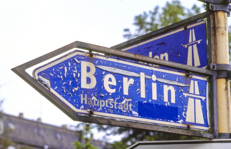 Ein Straßenschild mit Hinweis auf die Autobahn nach Berlin, unter dem Wort Berlin steht Hauptstadt, dahinter ist etwas überklebt.
