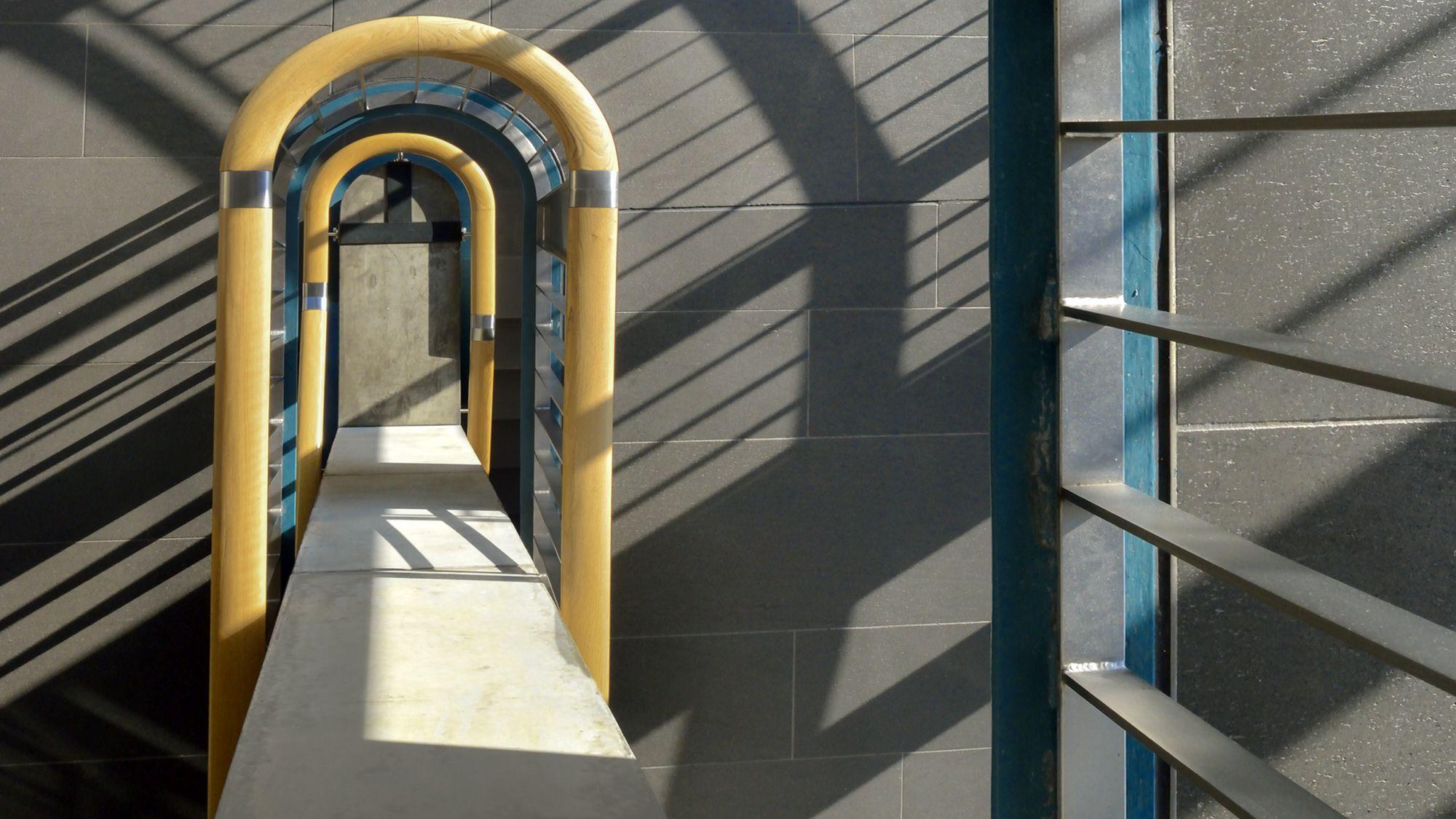 Ein gelbumrahmte Türflucht zwischen dunklen Granitwänden, Licht- und Schattenspiel