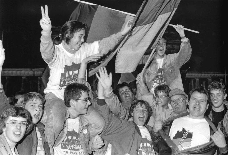 Jubelnde Menschen mit Deutschlandfahnen und T-Shirts mit dem Brandenburger Tor darauf.