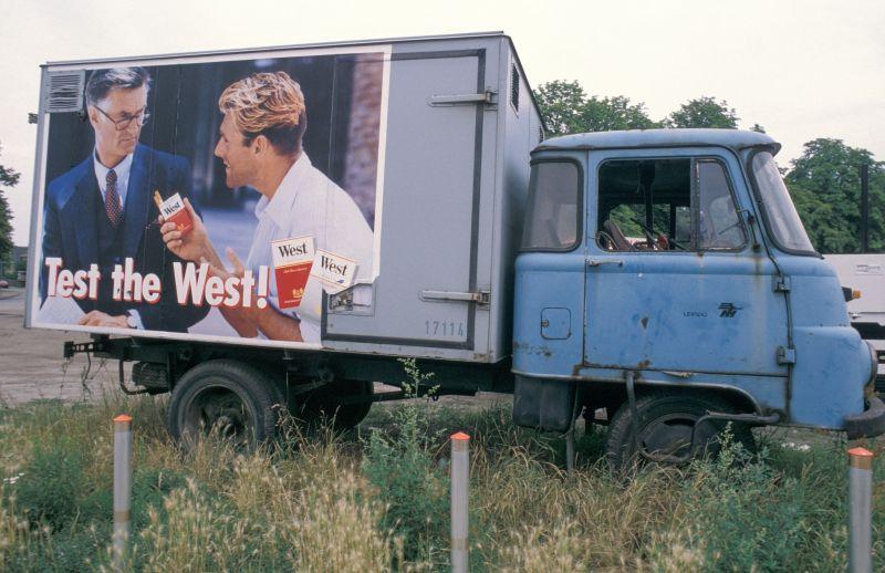 Das Autowrack eines Kleinlasters mit einer großflächigen Zigarettenwerbung mit dem Spruch Test the West.