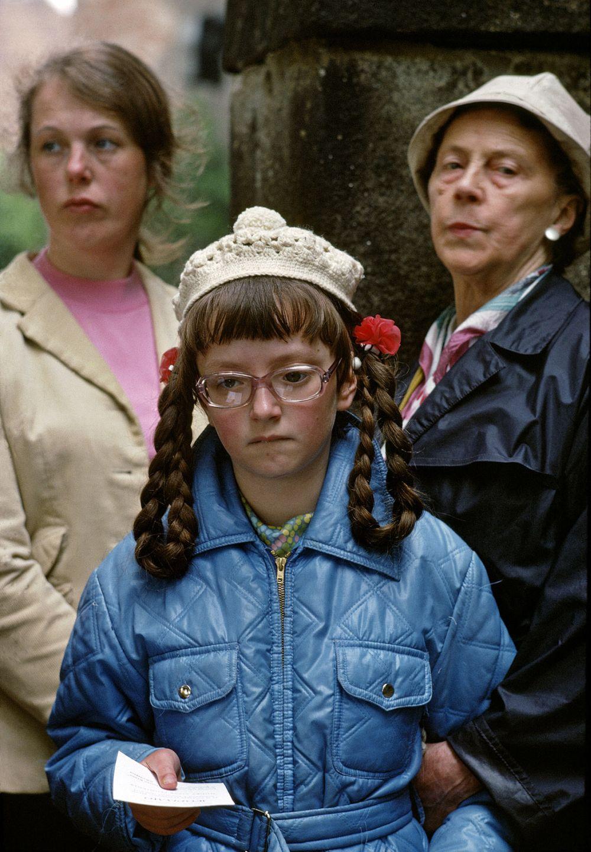 Fotografie 'Mädchen mit roten Nelken in den Zöpfen'