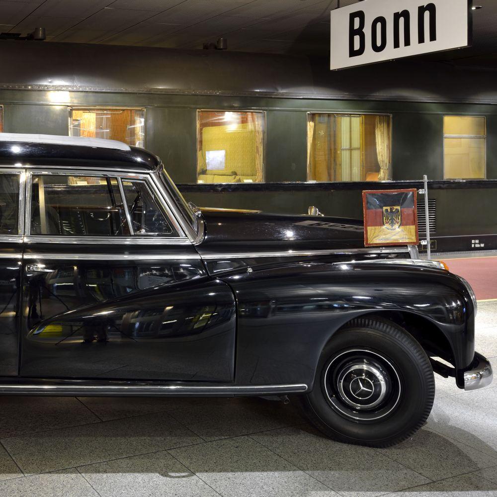 Im Vordergrund ein Stück der Motorhaube einer alten Mercedes-Limousine, im Hintergrund ein Eisenbahnwagon, oben ein Schild mit der Aufschrift Bonn.