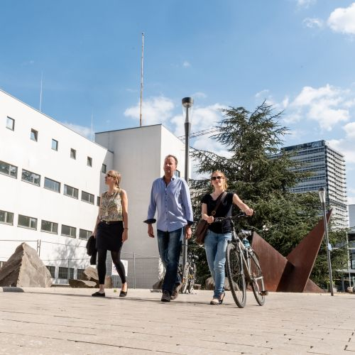 Zwei junge Frauen, eine davon mit Fahrrad und ein Mann, laufen über einen Platz, im Hintergrund ein weißes Gebäude und ein Hochhaus